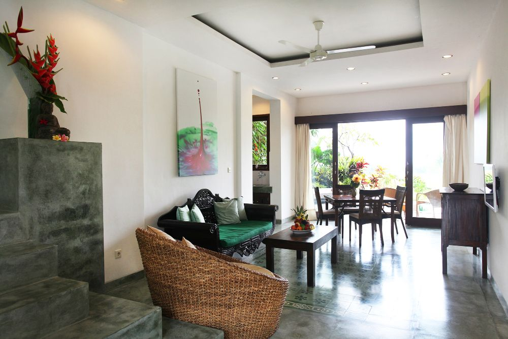 Villa Lotus spacious living room and dining area with kitchen visible to the right and sliding doors opening onto pool deck