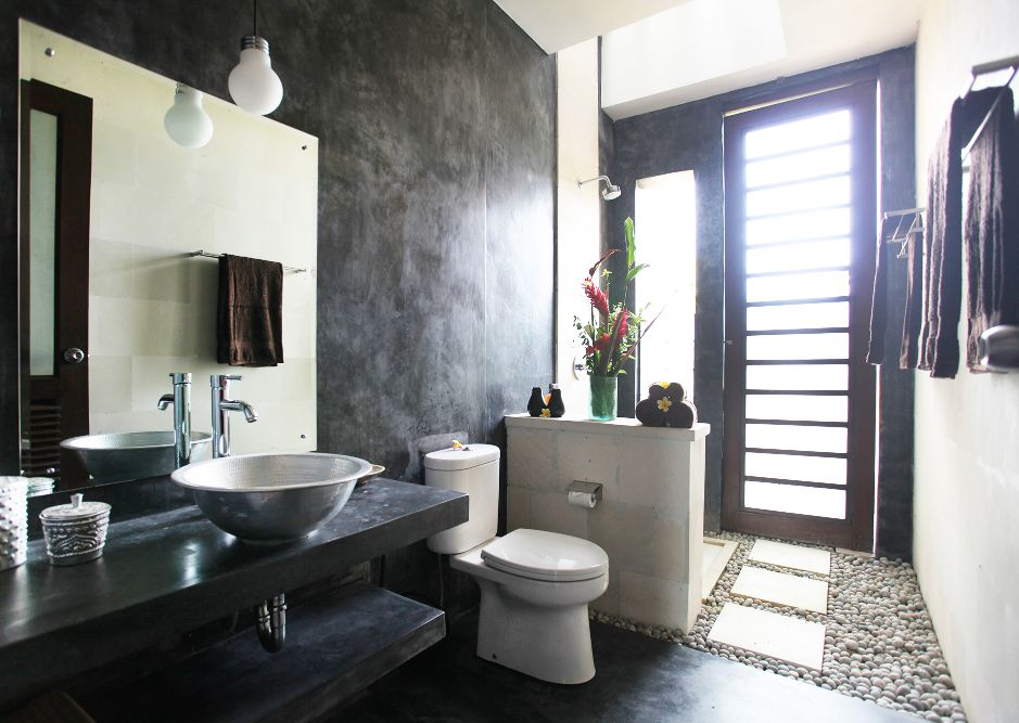 Villa Bamboo main bathroom with toilet, sink, shower and doorway out onto the pool area