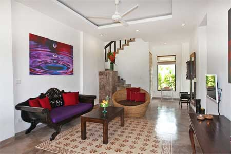 Villa Lotus living room with day bed, comfortable love seat, flat screen TV and stairs to upstairs bedroom visible