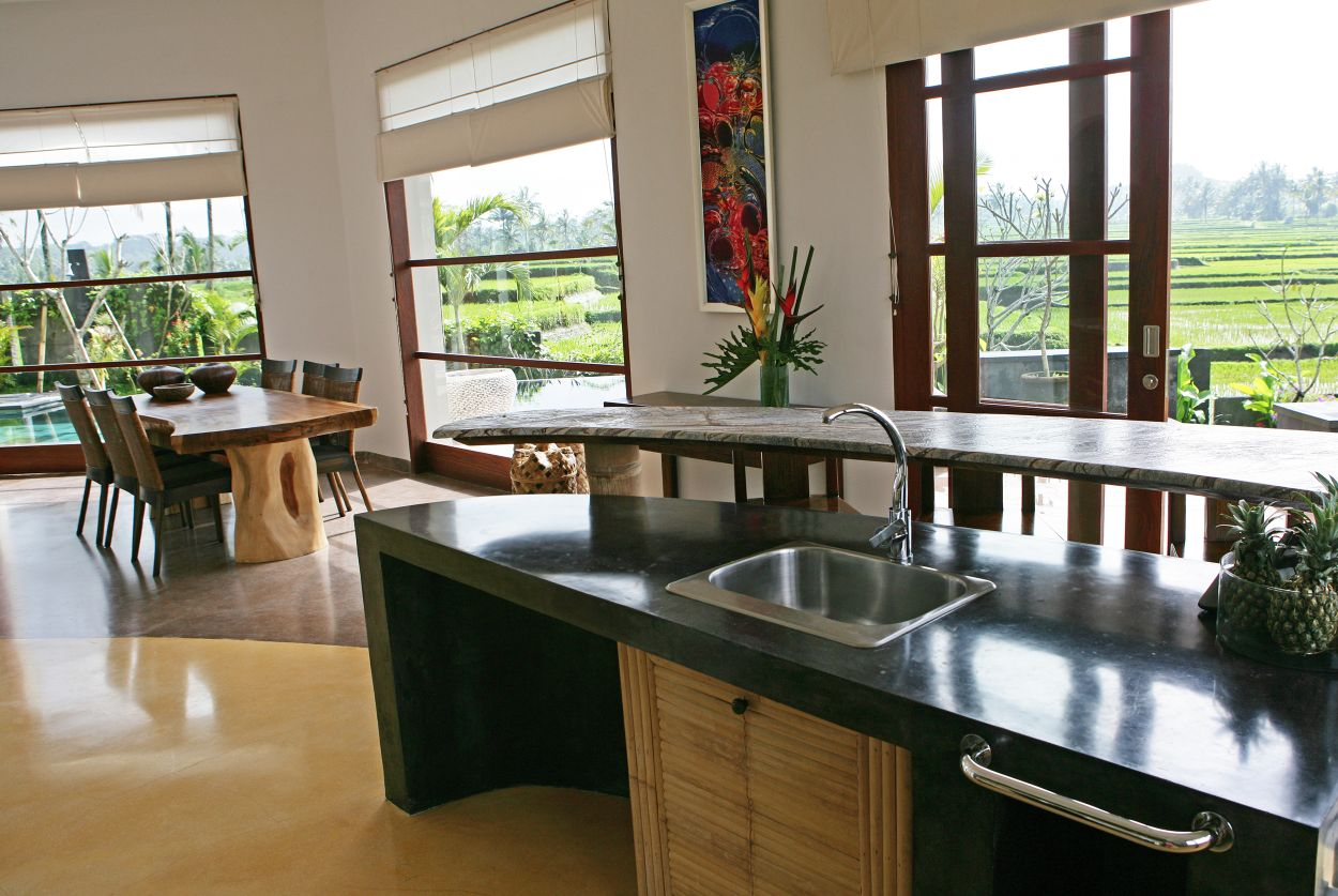 Villa Sari kitchen counter and island with dining table, swimming pool and rice paddies visible