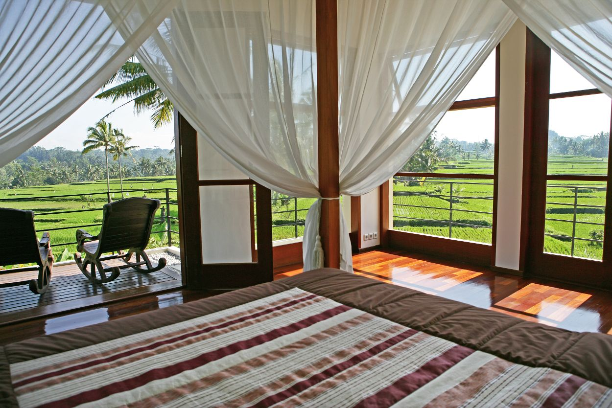 Villa Sari master bedroom solid wood fourposter king size bed, polished wood floors and double doors opening onto a balcony overlooking a sea of rice paddies