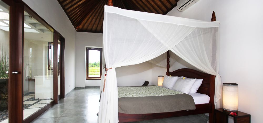 Villa Bamboo bedroom with queen size bed, ensuite and balcony with rice field view. Room has AC, Fan, mostiquo net and hot & cold water.