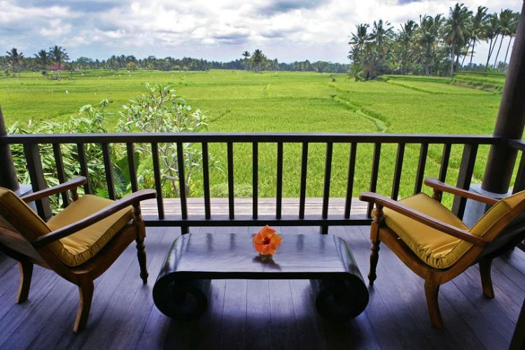 Villa Lotus upstairs balcony with comfortable reclining chairs and artisan low table; view of expansive rice fields, coconut trees and ocean in distance